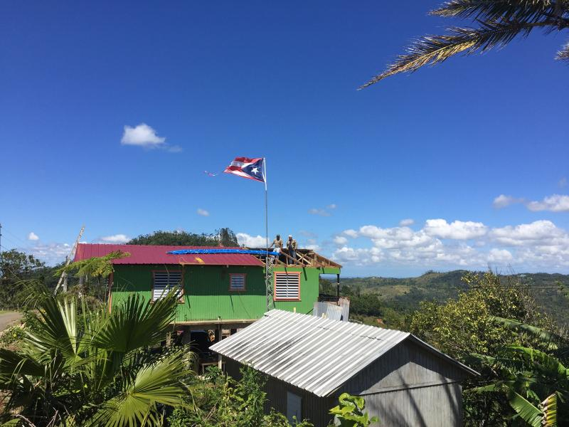 In the aftermath of Hurricane Maria, restorations are being made to a roof in Castañer, a village in Puerto Rico's central mountains. But recovery is slow.