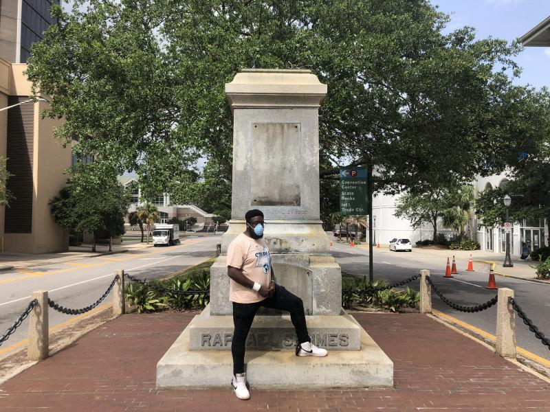 "Protest organizer DAntjuan Miller stands by the granite pedestal that remains of a monument to Confederate Navy Adm. Raphael Semmes in Mobile, Ala. ""It's like a weight that's lifted off now that it's gone,"" he says."