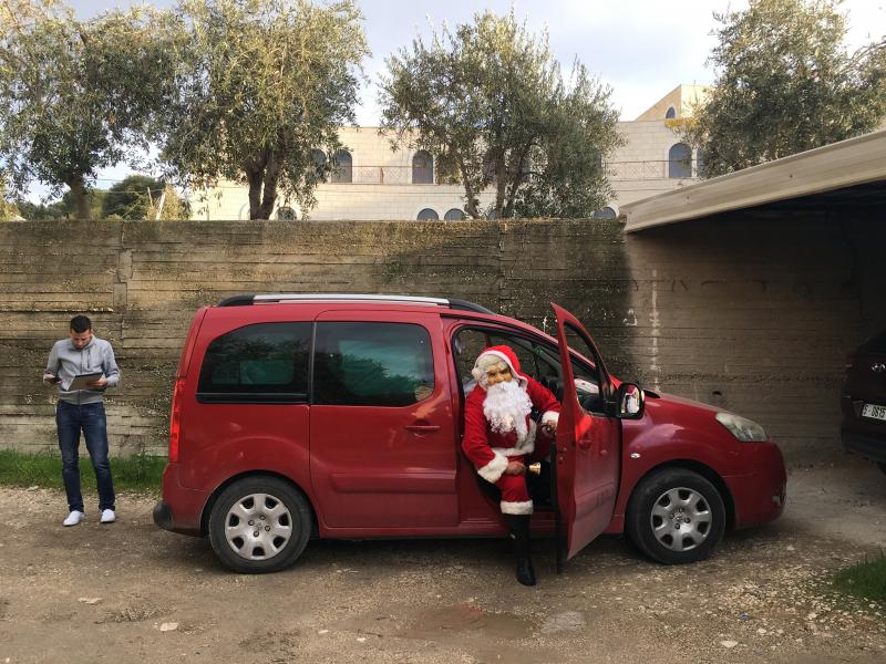 Sabri Canaan, 30, dons a Santa suit to deliver presents as Baba Noel (Father Christmas) on Christmas Eve in Bethlehem. His driver Mohammed Battah (left) briefs him on the list of children receiving gifts.
