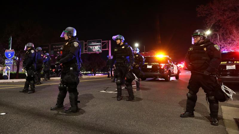 California Highway Patrol officers block an interstate entrance as protesters march. Police use of deadly force became a focus for advocates in California after the district attorney declined to prosecute the officers who fatally shot Stephon Clark, an un