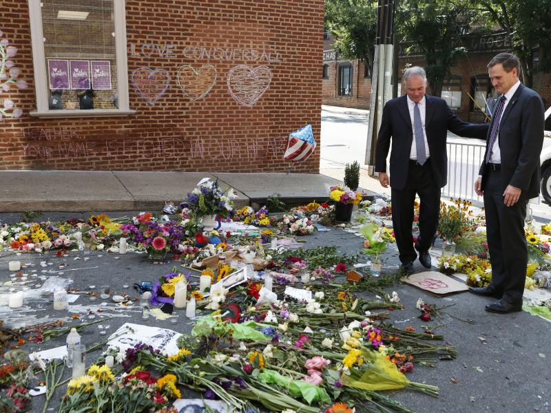 Sen. Tim Kaine, left, and then-Charlottesville mayor Michael Signer visit a temporary memorial Wednesday, Aug. 16, 2017, where Heather Heyer was killed when a car rammed into a crowd of people protesting a white nationalist rally Charlottesville, Va.