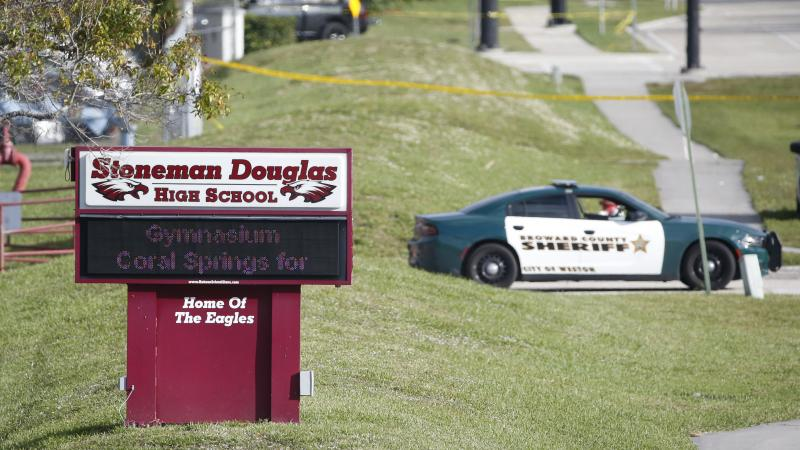 Law enforcement officers block off the entrance to Marjory Stoneman Douglas High School on Feb. 15 in Parkland, Fla. A day earlier a gunman opened fire in the school.