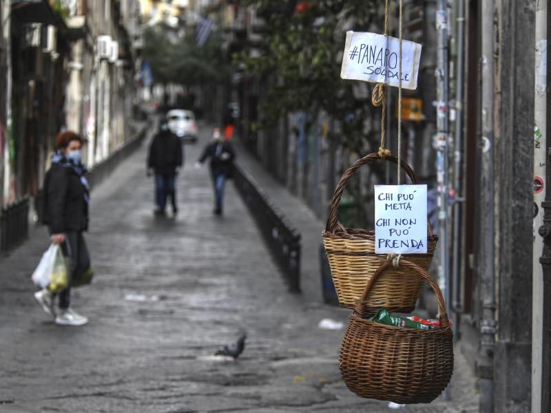 "A solidarity basket with a note reading ""Those who can, put something in, those who can't, help yourself"" is hung in the historic center of Naples."