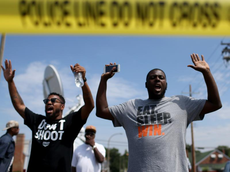 """The shooting of Michael Brown in Ferguson, Mo., also led to a series of protests. Many of them, like this protest on Aug. 19, featured people raising their arms and chanting, """"Hands up, don't shoot."""" But interactions between police and protesters were mor"""