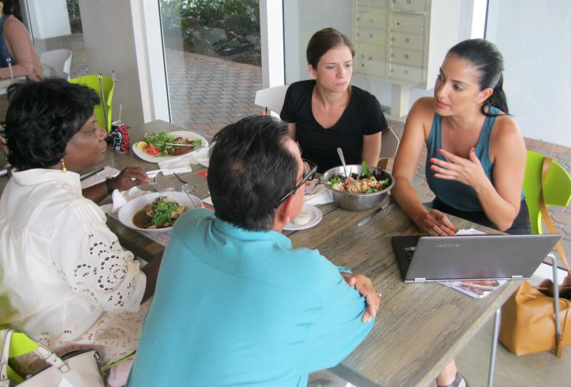 Miami swimwear entrepreneur Mel Valenzuela (right) explains online strategies to Cuban business owners Victor Rodriguez (middle) and Caridad Limonta (left) in Wynwood this month. Miami boutique owner Monica Minagorri (rear) watches.
