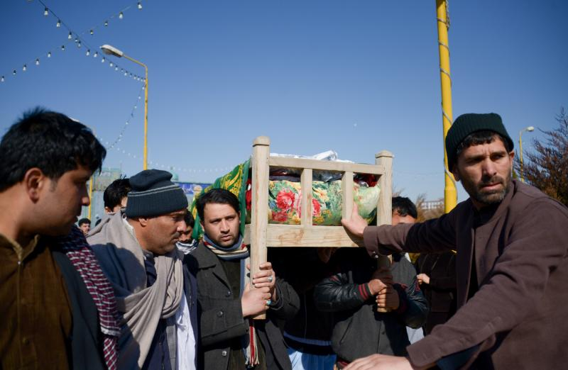 Mourners carry the coffin of one of six Afghan employees of the Red Cross killed in an attack in a remote northern province in February.