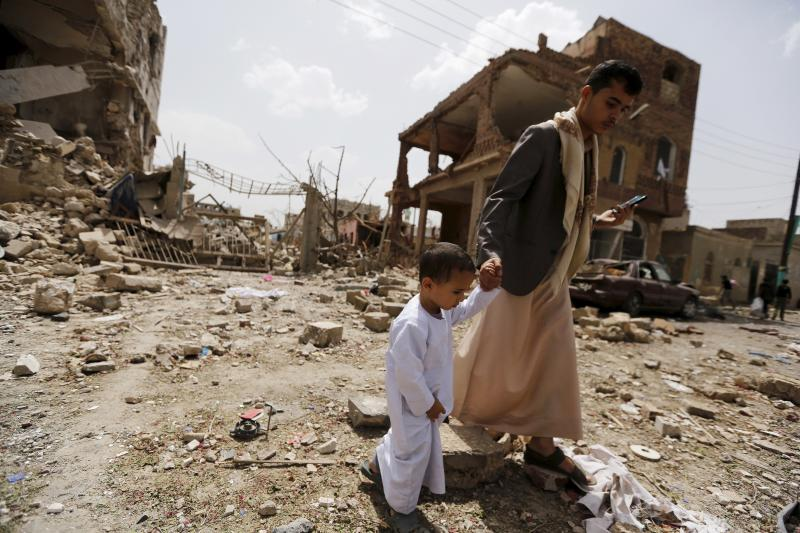 A man and a boy walk at a site hit by a Saudi-led air strike in Yemen's capital Sanaa on July 3. More than a million civilians have been displaced in recent fighting.