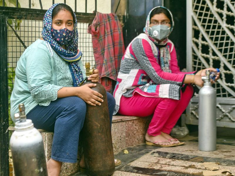 India has reported more than 20 million coronavirus cases, adding more than 2.6 million new cases in the past week alone. Here, women wait to refill empty oxygen cylinders in New Delhi. Oxygen shortages are blamed for deaths at even the best-equipped urba