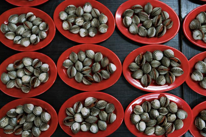 Plates of blood clams are on display at a stand in one of Jakarta's outdoor food courts.