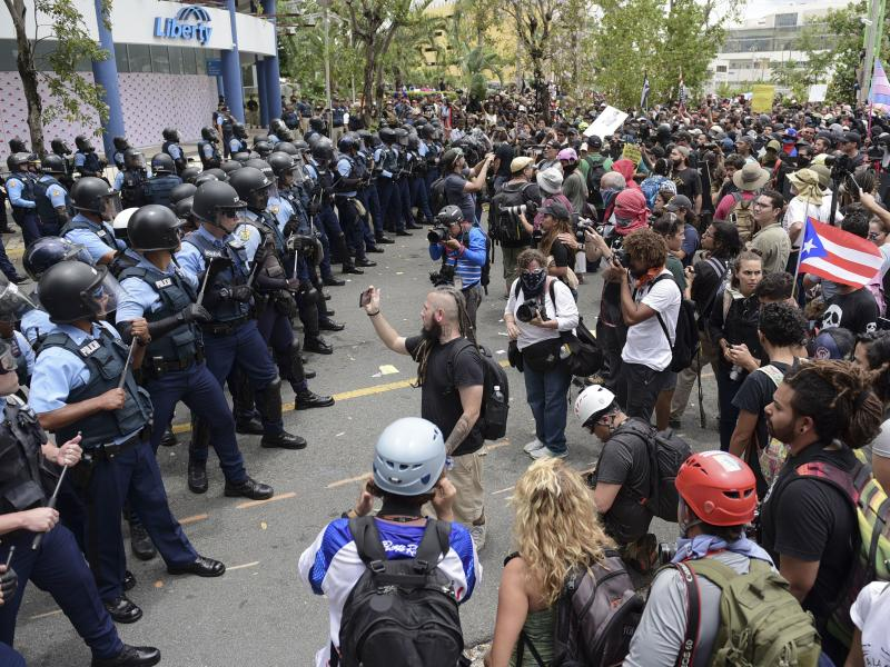 Police form a barrier against protesters during a May Day march Tuesday  in San Juan, Puerto Rico, to protest pension cuts, school closures and slow hurricane recovery efforts.