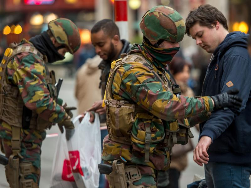 Policemen search passengers at the entrance of the De Brouckere metro station in Brussels on March 24, two days after the terrorist attack on the city.
