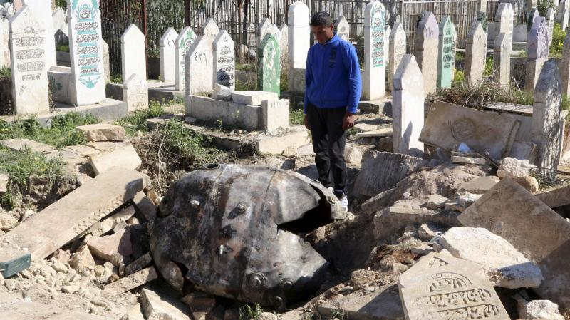 A man looks at an unexploded barrel bomb that landed in a cemetery after being dropped by forces loyal to Syria's President Bashar Assad in the northern Syrian city of Aleppo on Thursday.
