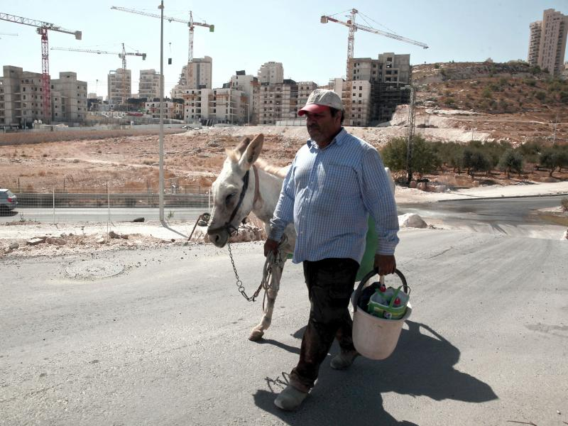 A Palestinian man walks near a construction site of a new housing unit in a neighborhood in East Jerusalem known to Jewish settlers as Har Homa and to Palestinians as Jabal Abu Ghneim. The Palestinians want East Jerusalem to be the capital of a future sta