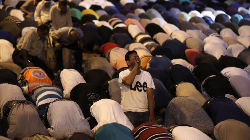 Palestinian Muslim worshippers pray outside an entrance to the Al-Aqsa mosque compound in Jerusalem's Old City on Sunday. They gathered to protest new Israeli security measures implemented at the holy site following an attack that killed two Israeli polic