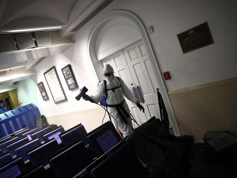 A member of the White House cleaning staff sanitizes the James S. Brady Press Briefing Room on October 5.