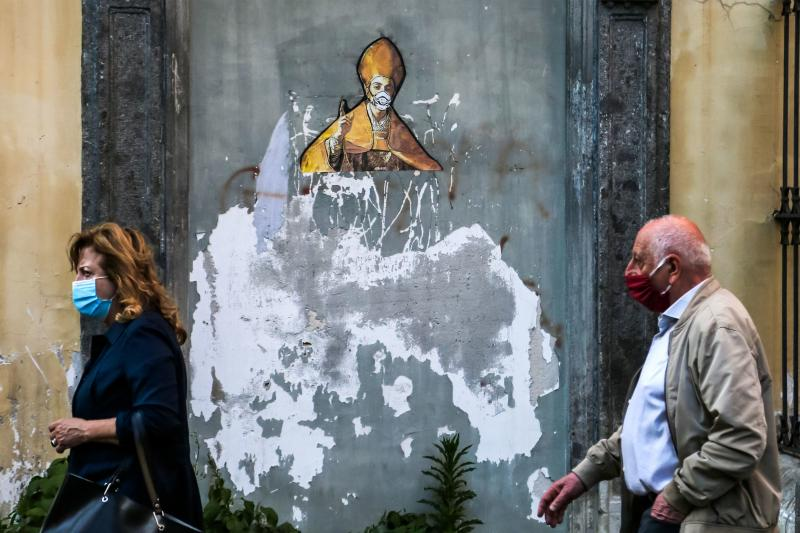 Pedestrians in face masks pass a mural in Naples depicting the city's patron saint, St. Gennaro, in a face mask too. Italy has set a timeline for lifting its strict coronavirus travel restrictions, after its outbreak overwhelmed medical centers across the
