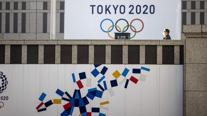 A pedestrian walks past an official Tokyo 2020 Olympic Games banner hanging on the Tokyo Metropolitan Government Building on Friday.