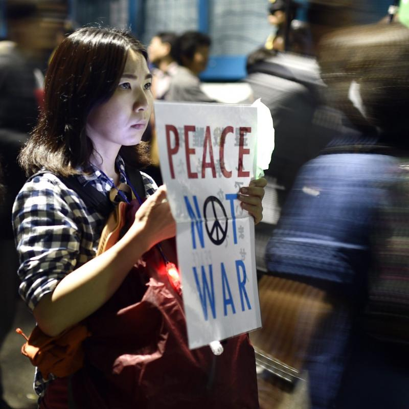 A young woman holds a placard protesting against controversial military reform bills outside Japan's parliament in Tokyo, Japan, on Friday. Lawmakers passed two measures to expand the role of Japan's military for the first time since World War II.