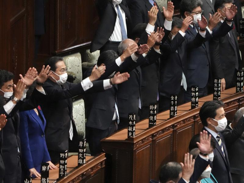 Japanese Prime Minister Fumio Kishida, forth from left, and other lawmakers give three cheers after dissolving the lower house, the more powerful of the two parliamentary chambers, during an extraordinary Diet session at the lower house of parliament Thur