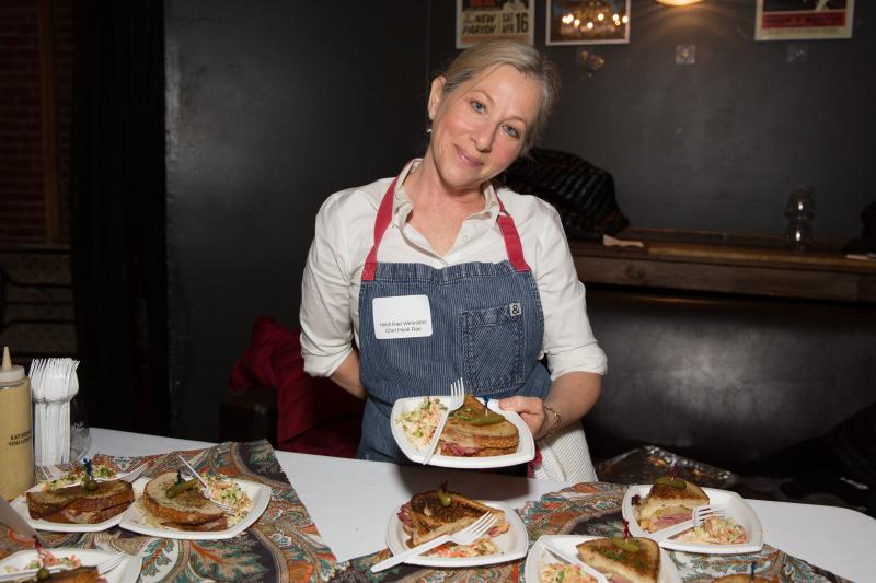 Chef Heidi Rae Weinstein holds a Reuben sandwich, complete with Swiss cheese — definitely a kosher no-no — at Trefa Banquet 2.0, an event held in San Francisco to commemorate a scandalous meal held in 1883 by newly ordained rabbis of the Jewish reform