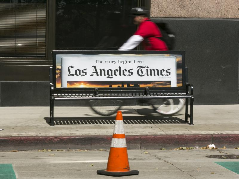 A cyclist rides on the sidewalk past a Los Angeles Times advertisement in downtown Los Angeles. The newspaper is being sued by employees alleging pay discrimination.