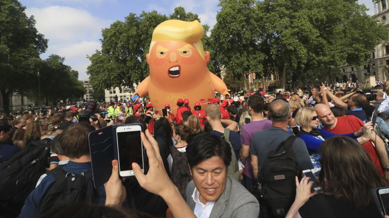 """A protest against President Trump in London's Parliament Square includes a giant balloon of """"Trump Baby"""" in a diaper on Friday. It flew high above the statutes of prominent historical figures including Winston Churchill, Mahatma Gandhi and Millicent Fawce"""