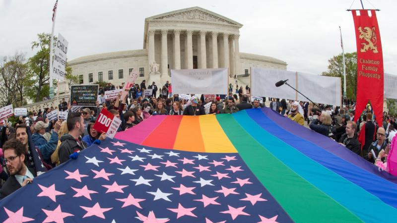 Protesters hold a pro-gay-rights flag outside the US Supreme Court on Saturday, countering the demonstrators who attended the March For Marriage in Washington, D.C. The Supreme Court meets on Tuesday to hear arguments over whether same-sex couples have a
