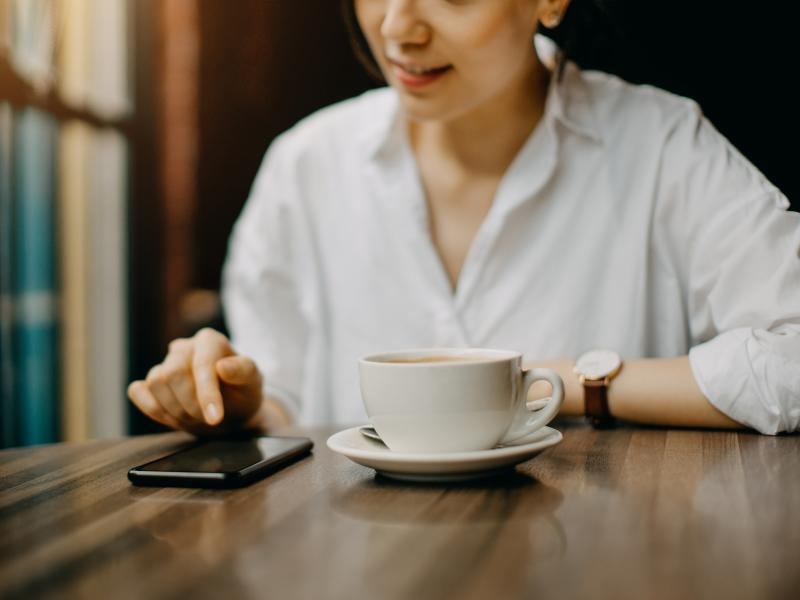 A young woman sits in cafe while text messaging on her smartphone.