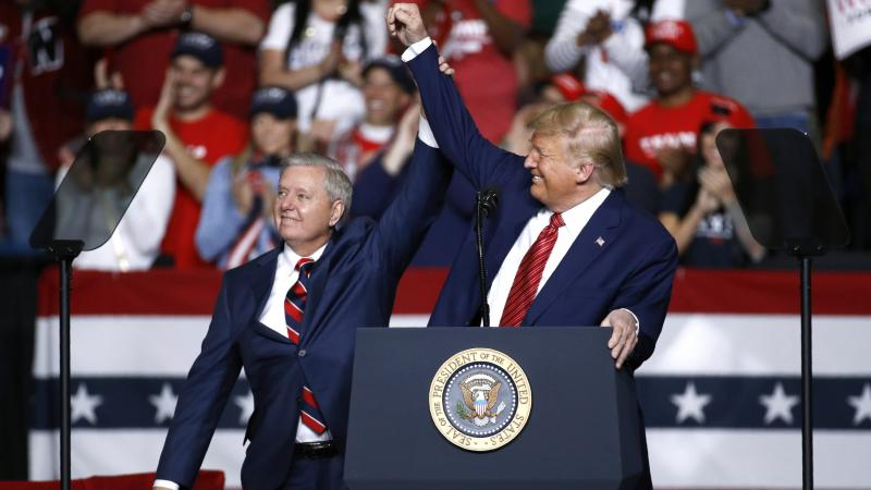 Sen. Lindsey Graham, R-S.C., stands onstage with President Trump during a Feb. 28 campaign rally in North Charleston, S.C. His allegiance to Trump has left some moderate voters feeling snubbed and switching allegiances to Democrat Jaime Harrison.