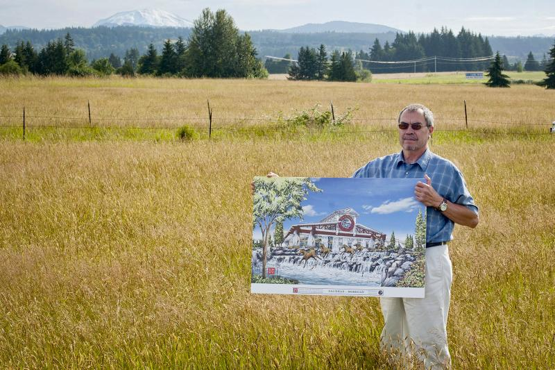 Tribal Chairman Bill Iyall stands on Cowlitz Tribe reservation land with a rendering of the casino the tribe hopes to build on the site near La Center, Washington, just north of Portland, Ore.