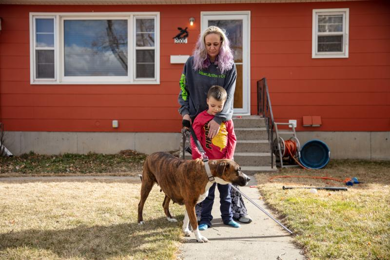 Barbara Gaught stands outside the home she's now renting in Billings, Mont., with her 5-year-old son, Blazen, and their dog, Arie. Gaught and her family were evicted from the mobile home they had owned outright and lived in for 16 years because they fell