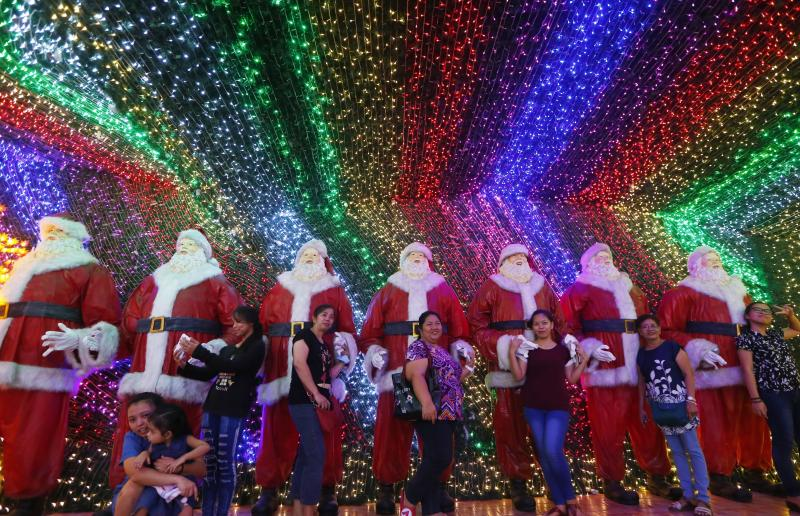 """Filipinos pose for souvenir shots at the """"Christmas House"""" owned by businessman Alexander Cruz in suburban Cainta, Rizal province, Philippines, on Dec. 12, 2017. The whole house, decorated with hundreds of thousands of LED lights, has attracted local and"""