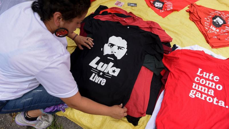 Street vendors display merchandise featuring former Brazilian President Luiz Inácio Lula da Silva, just outside the building in Curitiba where the leader served his prison sentence.