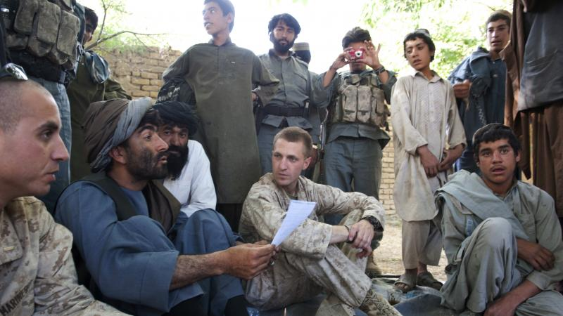 Jason Brezler, seated center, holds a meeting with local governors in Afghanistan in 2010. Brezler faced discharge after emailing classified documents over an insecure network. He challenged the Marine Corps' decision.
