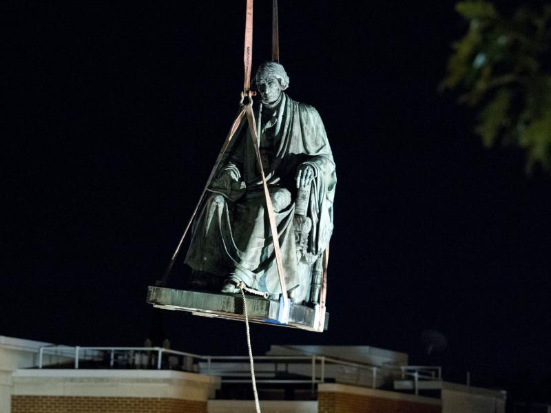 Workers use a crane to lift the monument dedicated to former  Chief Justice of the United States Roger Taney in Annapolis, Md., early Friday. The State House Trust voted Wednesday to remove the statue from its grounds.