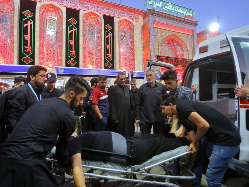 People evacuate an injured man after a walkway collapsed and set off a stampede as thousands of Shiite Muslims marked one of the most solemn holy days of the year in the holy city of Karbala, Iraq, on Tuesday.