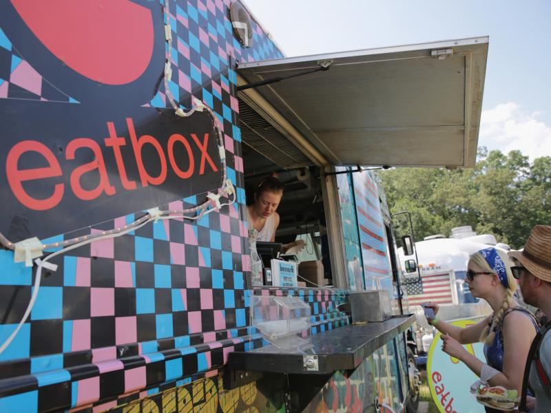 Festival goers order from a food truck during the Bonnaroo Arts And Music Festival on June 11, in Manchester, Tenn. Food trucks embody the startup culture but a new study suggests millennials are wary of starting businesses because of economic hardships.