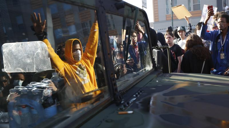 """A National Guard vehicle reflects a crowd of protesters Friday in Minneapolis, where Maj. Gen. Jon Jensen said that night's deployment """"was not enough"""" to handle the massive protests over the death of George Floyd."""