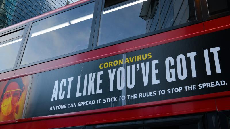 Moderna will test new COVID-19 vaccine booster doses, saying that while its vaccine should protect against variants found in the U.K. and South Africa, it isn't as effective against the South African strain. Here, a bus in London carries a sign telling pe