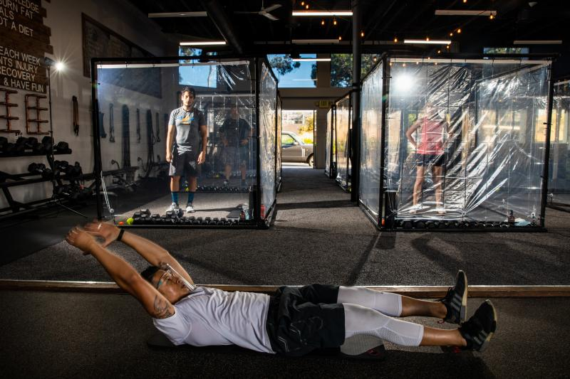 """Peet Sapsin directs clients inside custom built """"Gainz Pods"""", during his HIIT class, (high intensity interval training), at Sapsins Inspire South Bay Fitness, Redondo Beach, California, Wednesday, June 17, 2020."""