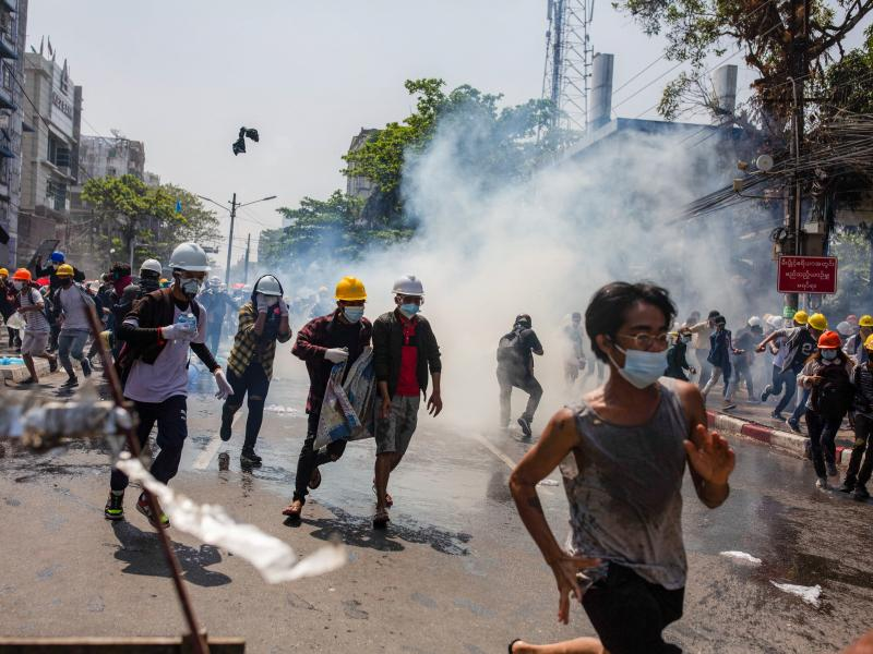 Anti-junta protesters run from teargas fired by police during a demonstration in Yangon on Monday. At least 18 people were killed over the weekend as Myanmar police reportedly used live ammunition against protesters.