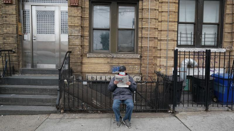 A man wearing a surgical mask reads the newspaper on the sidewalk late last month in New York City. The city's leaders said Thursday that social distancing is still necessary.