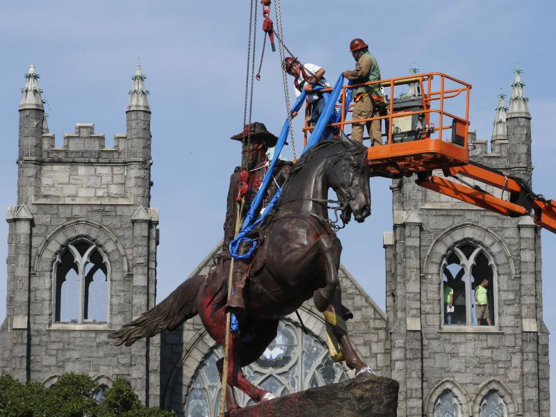 Crews attach straps in July to the statue of Confederate Gen. J.E.B. Stuart in Richmond, Va. The statue was one of several that were removed by the city in 2020 following nationwide protests against systemic racism.