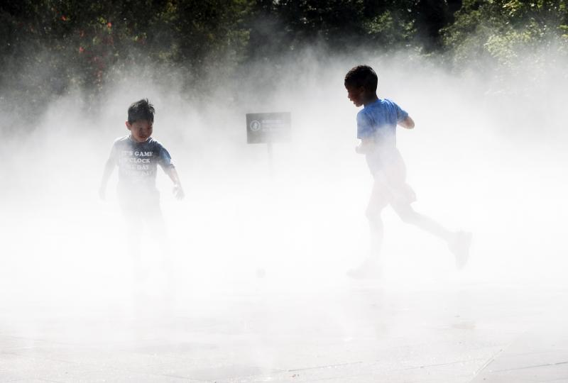 Children beat the heat Thursday in a misting pool at a park in Queens as temperatures reach into the 90s in New York City.