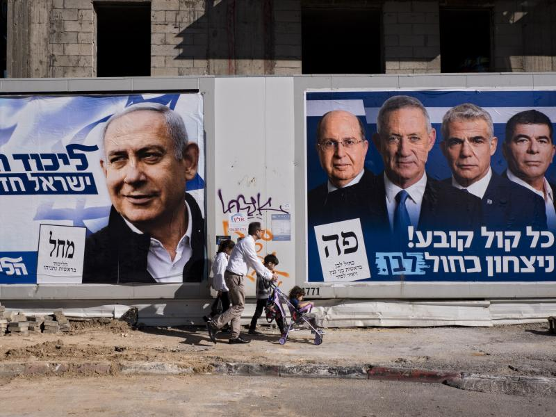 People walk by election campaign billboards in Tel Aviv, Israel, showing Israeli Prime Minister Benjamin Netanyahu (billboard on left) alongside the Blue and White alliance leaders (billboard on right, from left to right), Moshe Yaalon, Benny Gantz, Yair