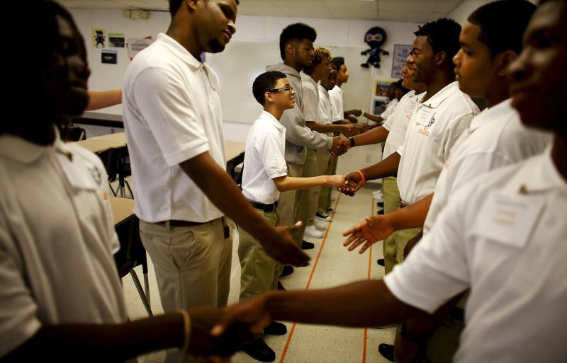 Ninth graders at George Washington Carver Collegiate Academy learn to shake hands and greet each other during the first day of school in New Orleans.