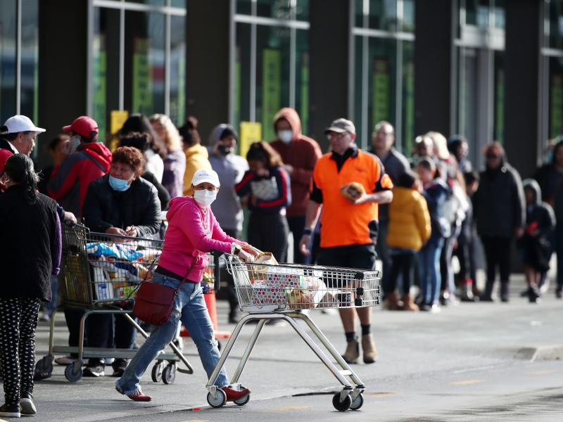 People line up outside a supermarket in a suburb of Auckland, New Zealand, on Wednesday before a three-day lockdown goes into effect. Four new COVID-19 cases were diagnosed in Auckland, and an additional four probable cases have been identified.