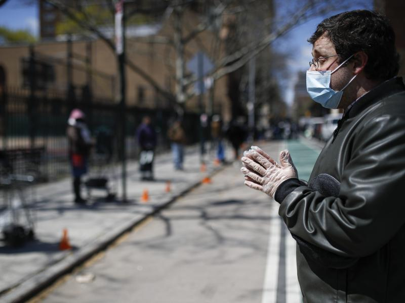 Christopher Love, general manager of the Covenant Mercy Mission, leads a prayer beside a line of visitors waiting for food donations at Manor Community Church on Saturday in New York. An additional 758 people died from the coronavirus over the past 24 hou