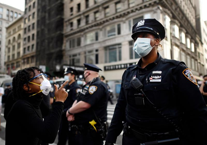 Shouting protesters face NYPD officers during a Black Lives Matter demonstration last summer in New York City, in outrage over the death of a Black man in Minnesota who died after a white policeman knelt on his neck for several minutes.