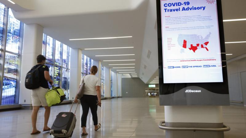 Arriving travelers walk by a COVID-19 travel advisory sign in the baggage claim area at New York City's LaGuardia Airport. New York state is requiring travelers from states on its quarantine list to show proof that they've completed a form with their cont
